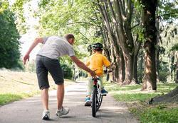 Foto av far med sønn på sykkel