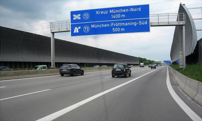 Høje buede støjskærme hvor den tyske Motorvej A9 passerer tæt forbi et boligområde nord for München. Skærmene er opsat for at kunne overholde gældende støjgrænser for boligerne.