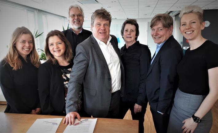 Gunnar Lindberg (i midten) har nettopp signert kontrakten som sier at han tar en ny periode i TØIs direktørstol. Her står Lindberg sammen med TØI-styremedlemmene (fra venstre) Sunniva Frislid Meyer, Anne Iren Fagerbakke (styreleder), Svein Bråthen, Jane Summerton, Ole A. Hagen og Kjersti Øksenholt. Styremedlem Ola Henrik Strand var ikke til stede da bildet ble tatt. Foto: Harald Aas